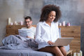 Smiling girl using a laptop while her boyfriend is reading Royalty Free Stock Photo