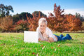Smiling girl using laptop outdoors Royalty Free Stock Photo
