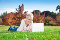 Smiling girl using laptop outdoors. Stock Image