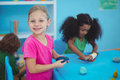 Smiling girl using modelling clay at their desk Royalty Free Stock Images