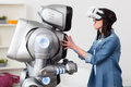 Smiling girl using virtual reality device what is it cheerful delighted and having fun while touching the robot Stock Photos