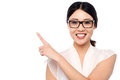 Smiling girl wearing eyglasses pointing away young cheerful with eyeglasses over white background Stock Photography