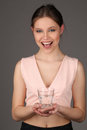 Smiling girl wearing pink top holding glass of water. Close up. Gray background Royalty Free Stock Photo