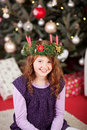 Smiling girl wearing an xmas candle wreath young sitting on the carpet in front of a decorated christmas tree a on her head and Royalty Free Stock Photos