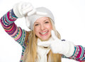 Smiling girl in winter clothes framing with hands isolated on white Stock Photos