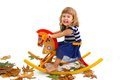 Smiling girl on a wooden horse Royalty Free Stock Image