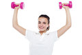 Smiling girl working out. Dumbbells above her head Stock Photography