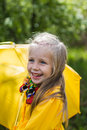 Smiling girl in a yellow dress with an umbrella on a rainy spring sunny day Royalty Free Stock Photo