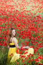 Smiling girl with yellow scarf in poppy field Royalty Free Stock Photo