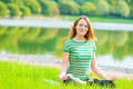 Smiling girl-yogi performs exercises in a green park Royalty Free Stock Photo