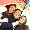 Smiling girlfriends under umbrella Royalty Free Stock Photo