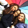 Smiling girlfriends under umbrella Royalty Free Stock Photos