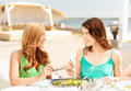 Smiling girls in cafe on the beach summer holidays and vacation concept Royalty Free Stock Image