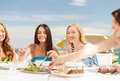 Smiling girls in cafe on the beach summer holidays and vacation concept Stock Images
