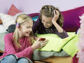 Smiling girls with cellphone in bedroom two young looking at mobile phone Stock Photo