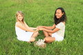 Smiling girls sitting on grass Royalty Free Stock Photo