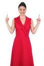 Smiling glamorous model in red dress pointing up on white background Stock Image