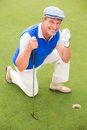 Smiling golfer kneeling on the putting green Royalty Free Stock Photo