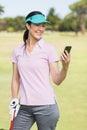 Smiling golfer woman using phone Royalty Free Stock Photo