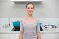 Smiling gorgeous blonde looking at camera standing in kitchen Stock Photos