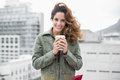 Smiling gorgeous brunette in winter fashion holding disposable cup on urban background Stock Image