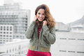 Smiling gorgeous brunette in winter fashion looking at camera on urban background Stock Photo