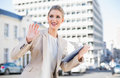 Smiling gorgeous businesswoman holding tablet pc waving outdoors on urban background Royalty Free Stock Photography