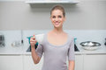 Smiling gorgeous model looking at camera holding mug standing in kitchen Stock Photography