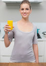 Smiling gorgeous model looking at camera holding orange juice standing in kitchen Stock Photography