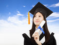 Smiling graduate woman holding degree cloud background Stock Photo
