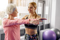 Smiling grandmother dealing with coach in gym Royalty Free Stock Photo