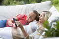 Smiling grandmother and granddaughter laying on outdoor sofa with digital tablet Royalty Free Stock Photo