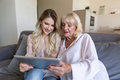 Smiling grandmother and her granddaughter looking at a tablet Royalty Free Stock Photo