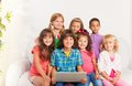 Smiling group of kids with laptop happy years old sitting on the coach and looking at camera Royalty Free Stock Photos