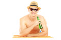 Smiling guy with hat lying on a beach towel and drinking cold be beer isolated white background Royalty Free Stock Photography