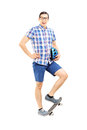 Smiling guy holding a helmet and standing on a skate board full length portrait of isolated white background Royalty Free Stock Photography