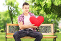 Smiling guy sitting on a bench and holding a red heart in park shaped object Royalty Free Stock Photography
