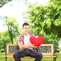 Smiling guy sitting on a bench and holding a red heart in park shaped object shot with tilt shift lens Stock Image