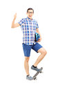 Smiling guy standing on a skate board and giving thumb up full length portrait of isolated white background Stock Photos