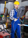 Smiling guy using welder for construction work Royalty Free Stock Photo