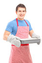 Smiling guy wearing cooking mittens and apron Royalty Free Stock Photo