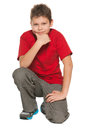 Smiling handsome boy red shirt sits floor white background Stock Photo
