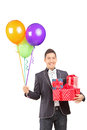 Smiling handsome guy with bow tie holding presents and balloons bunch of isolated on white background Royalty Free Stock Images