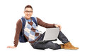 Smiling handsome guy sitting on a floor with laptop and looking at camera isolated white background Stock Images