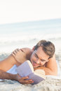 Smiling handsome man on the beach reading Royalty Free Stock Photo