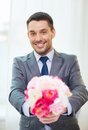 Smiling handsome man giving bouquet of flowers spring and happiness concept fresh Royalty Free Stock Image