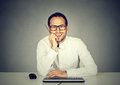 Smiling handsome man sitting in front of computer keyboard Royalty Free Stock Photo