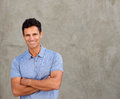 Smiling handsome man standing by wall with arms crossed Royalty Free Stock Photo