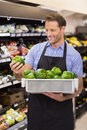 Smiling handsome worker taking a box with vegetable Royalty Free Stock Photo