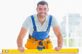 Smiling handyman using spirit level in office Royalty Free Stock Photo
